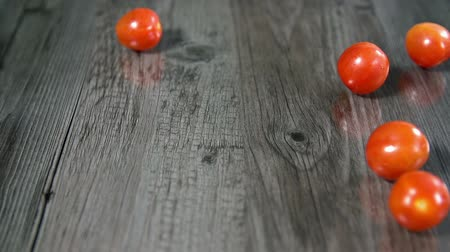 warzywa : Small tomatoes roll into the screen in slow motion