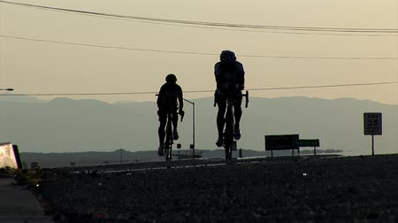 cyclists : Two competing cyclists approach the camera at the dawn