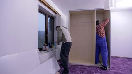 traje de passeio : Two guys trying to assemble the closet Stock Footage