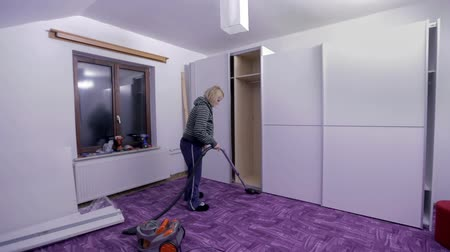 traje de passeio : Woman vacuums the room with new closets Stock Footage
