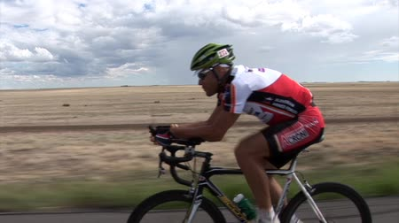 hareketli : USA - JUNE 2009: Driving by cyclist. Longest bicycle competition over United States of America - RAAM in 2009.