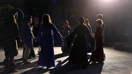 средневековый : CELJE, Slovenia - August 2012: People dancing in circle under the spotlights at night. Medieval festival with reenactment of fighting knights, swordsmen and spearmen, cavalry.
