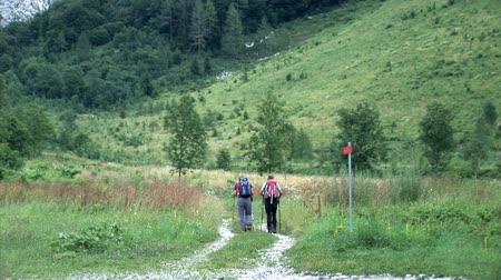 поход : Two older hikers are walking down the path