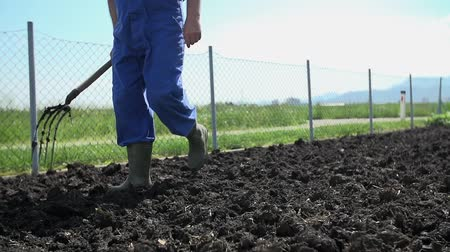 farm equipment : Close ups slow motion shot of gardener walking on the manure on the field of his home garden.