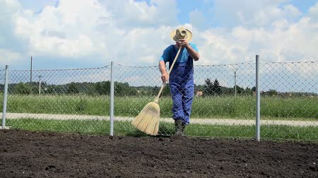 Łopata : Farmer using the brand new broom to sweep around the soil