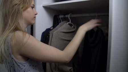 medo : Young woman is picking the clothes and finds a skeleton laying in the wardrobe.