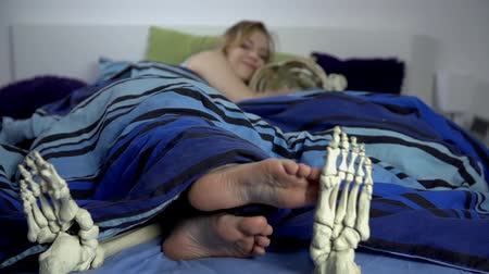 hálószoba : Woman slides with her toes across the skeletons feet. Attractive woman sleeps with skeleton and flirts with him in bed, with sexual desire. Slow motion jib shoot.