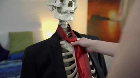 krawat : Woman ties up the tie to a skeleton. Dressing up the skeleton in nice business clothes, a tie and a hat in slow motion. Wideo