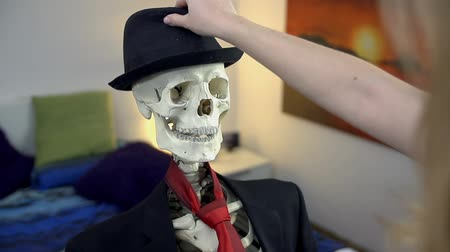 krawat : Lady dresses the skeleton. Dressing up the skeleton in nice business clothes, a tie and a hat in slow motion.