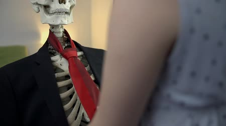 krawat : Young woman dresses up the dead guy. Dressing up the skeleton in nice business clothes, a tie and a hat in slow motion. Wideo