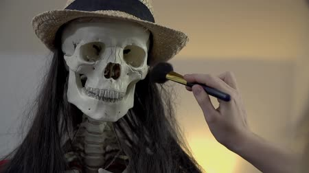 csontváz : Female hand uses brush to put make up on a skull