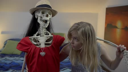 szomorúság : Girl braces herself with the arm of female skeleton Stock mozgókép