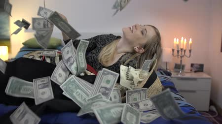 elcsábít : Female smiles with a bunch of cash in her hands laying on the bed