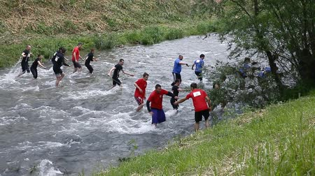 cruzamento : CELJE, SLOVENIA - MAY 2014: Gladiator games with obstacles while running on track. Teams crossing the river