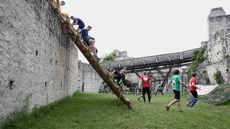 soutěže : CELJE, SLOVENIA - MAY 2014: Gladiator games with obstacles while running on track. Teams climbing down the ladder