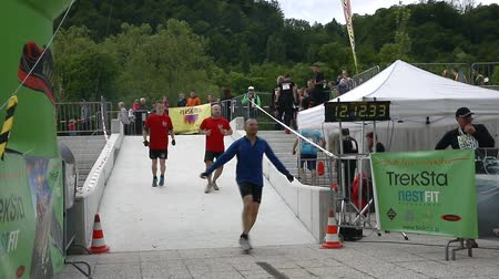 acabamento : CELJE, SLOVENIA - MAY 2014: Gladiator games with obstacles while running on track. People arriving to the finish line Stock Footage