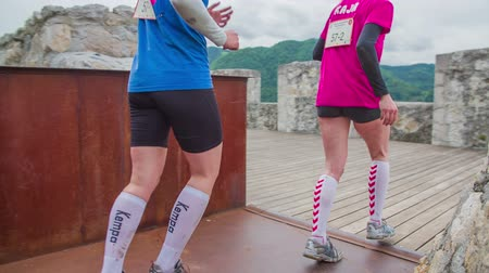 sock : CELJE, SLOVENIA - MAY 2014: Gladiator games with obstacles while running on track. Man and woman running through castle Stock Footage