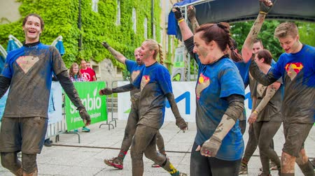 acabamento : CELJE, SLOVENIA - MAY 2014: Gladiator games with obstacles while running on track. Team arriving to the finish line