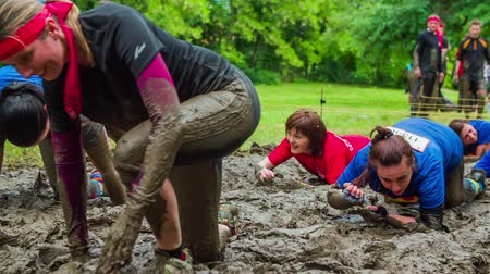 obstacles : CELJE, SLOVENIA - MAY 2014: Gladiator games with obstacles while running on track. People dragging through mud as part of obstacle course