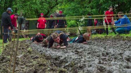 гонка : CELJE, SLOVENIA - MAY 2014: Gladiator games with obstacles while running on track. People crawling through mud as part of obstacle course