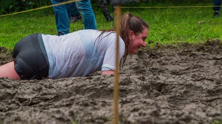 kurs : CELJE, SLOVENIA - MAY 2014: Gladiator games with obstacles while running on track. Woman crawling through mud as part of obstacle course Wideo