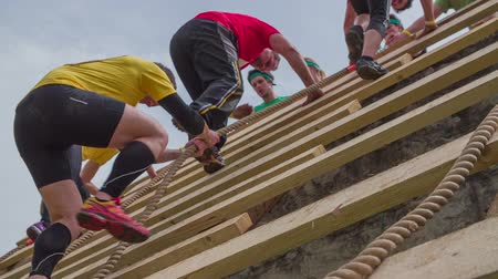kurs : CELJE, SLOVENIA - MAY 2014: Gladiator games with obstacles while running on track. Group of people running through obstacle course