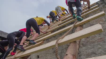 obstacles : CELJE, SLOVENIA - MAY 2014: Gladiator games with obstacles while running on track. Group of people climbing down ladder as part of obstacle course