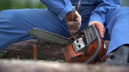 unscrewing : Fixing chainsaw in slow motion. Chainsaw broken while cutting, person unscrew chain and repair it. Stock Footage