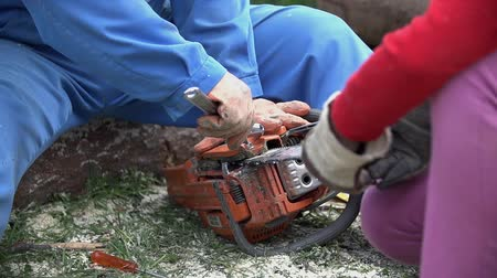 unscrewing : Second person help fix chainsaw holding chain. Broken chainsaw while cutting logs. Slow motion unscrewing chain. Stock Footage