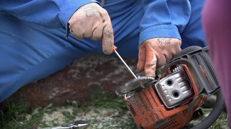 unscrewing : Cleaning chainsaw chain close up slow motion. Removing sawdust from chainsaw with screwdriver in slow motion. Stock Footage
