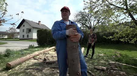 günlüğü : Carry heavy log in slow motion. Front shot tracking man in blue collar working clothes carrying cutted timber to pile for winter heating. Stok Video