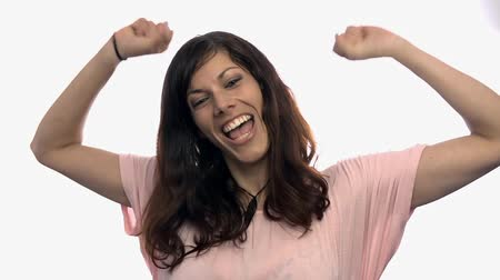 bílý : Woman clapping and rejoicing on white background. Attractive female jumping from happiness in slow motion