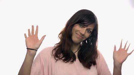 olá : Attractive woman saying hello with waving hands. Portrait shot of young female waving in to camera on white background in slow motion.