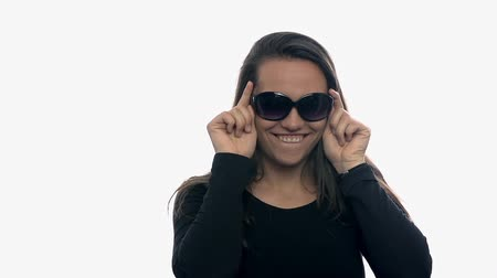 tonları : Attractive young woman winking behind sunglasses. Brown hair female with sunglasses puts down and winks on white background slow motion. Stok Video