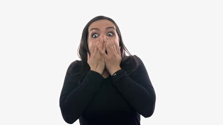 výraz : Woman shocked on white background. Attractive woman portrait is shocked and puts hands over mouth, looks scared.