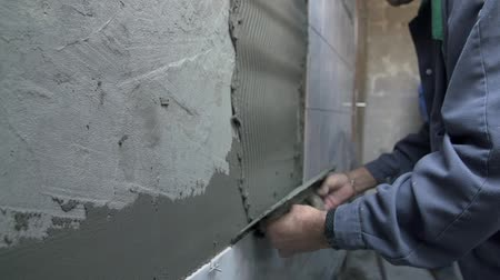 молоток : Putting glue on the wall. Man is putting special concrete stick to bathroom wall with special ceramists tool Стоковые видеозаписи