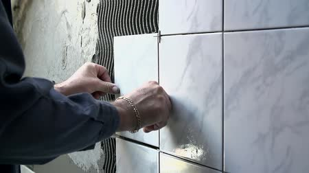 çini : Ceramist puts tile on the wall. Professional ceramist is laying big grey ceramic tile on the wall full of other ceramic tiles Stok Video