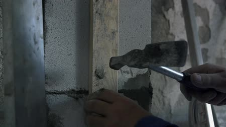 levelling : Man levels the concrete wall. Man is levelling concrete wall using usual piece of wood and special hammer