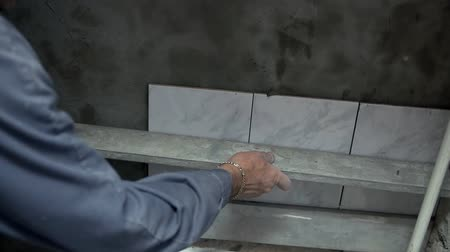 çini : Checking the straightness of tiles . Worker is checking the straightness of the laid ceramic tiles with special and accurate device Stok Video