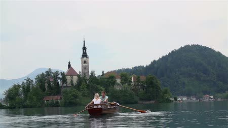 veslování : Couple on boat with church on island in background. Wide shot of boy and girl rowing on boat and enjoying romantic view of Bleds island.