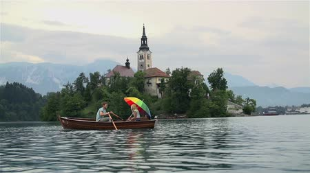 романтика : Young couple in love on a boat with church in background. Wide slow motion shot of lake in Bled and couple in romantic atmosphere. Стоковые видеозаписи