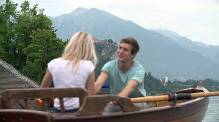 relação : Couple rowing on lake with focus on Bled castle in background. Happy romantic relationship with boy and girl enjoying time on lake in slow motion.