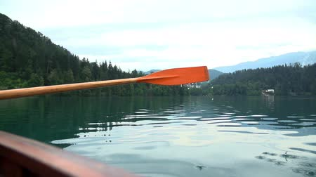 Строки : Boat paddle row in close up slow motion. Water drops falling from paddle while rowing on lake.