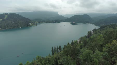 остров : Wide aerial shot of big Bled lake with island in the middle. Flying above the woods with view on lake on a very bad weather.