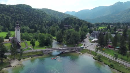 slovinsko : Descending to kayakers in lake with church and bridge in background. Aerial footage of Bohinj church and lake while people in kayak rowing.