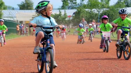 helmets : VRHNIKA, SLOVENIA - AUGUST 2014: Kids on bikes racing towards the camera. Bicycle competition for little kids on track, bicycling very fast. Stock Footage