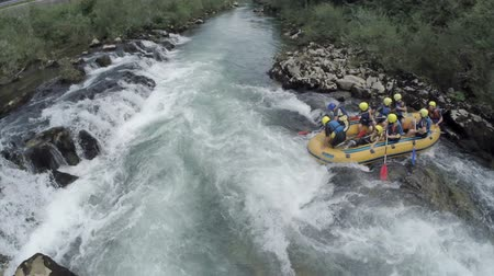 overcome : OSILNICA, SLOVENIA - AUGUST 2014: Rafting boat start the race in canyon. Rafting group of adventure people start the race after aground on the rocks on the canyon river