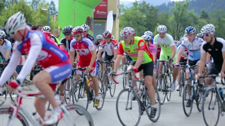 francja : VRHNIKA, SLOVENIA - JUNE 2014: Big group of professional cyclist passing the camera. Bicycle competition with cyclist speeding up after start. Close up on competitors with helmets and professional bikes.