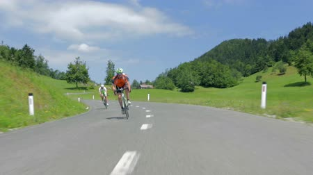 francja : VRHNIKA, SLOVENIA - JUNE 2014: Cyclist driving through corners very fast. Driving in front of bicycle competitors speeding down the hill through green corners in countryside. Wideo