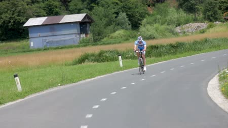 cyclists : VRHNIKA, SLOVENIA - JUNE 2014: Bicyclist driving in beautiful nature landscape. Empty road with lonesome cyclist speeding with green lawn in background on a sunny day.